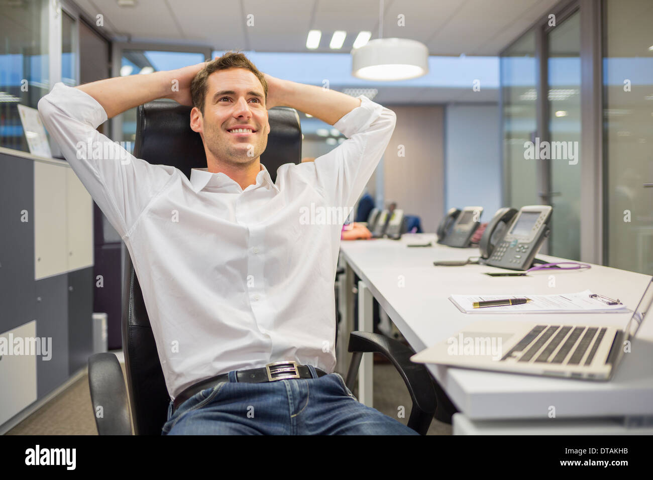 Happy businessman resting and relaxing at his office - Stock Image