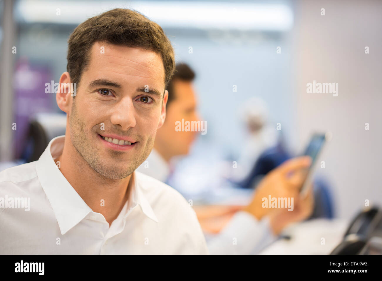Portrait of cheerful businessman in office, looking camera - Stock Image