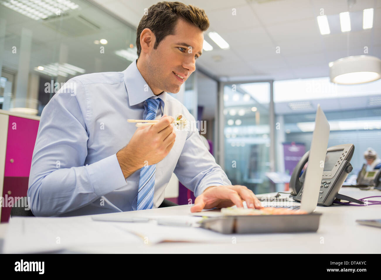 Businessman eating sushi in office - Stock Image
