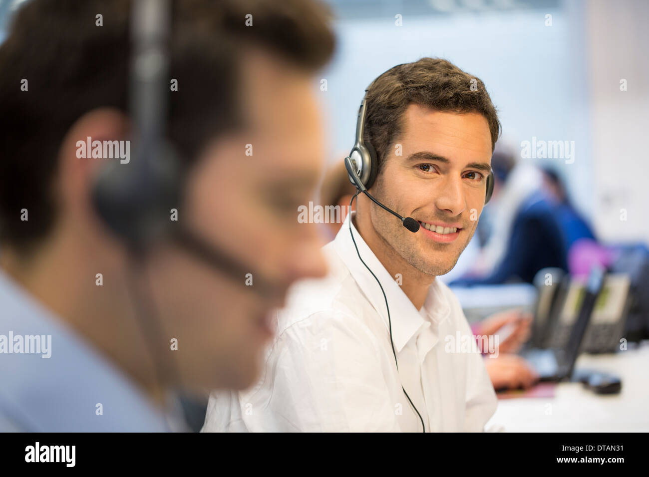 Portrait of Businessman in office on phone with headset, looking camera - Stock Image