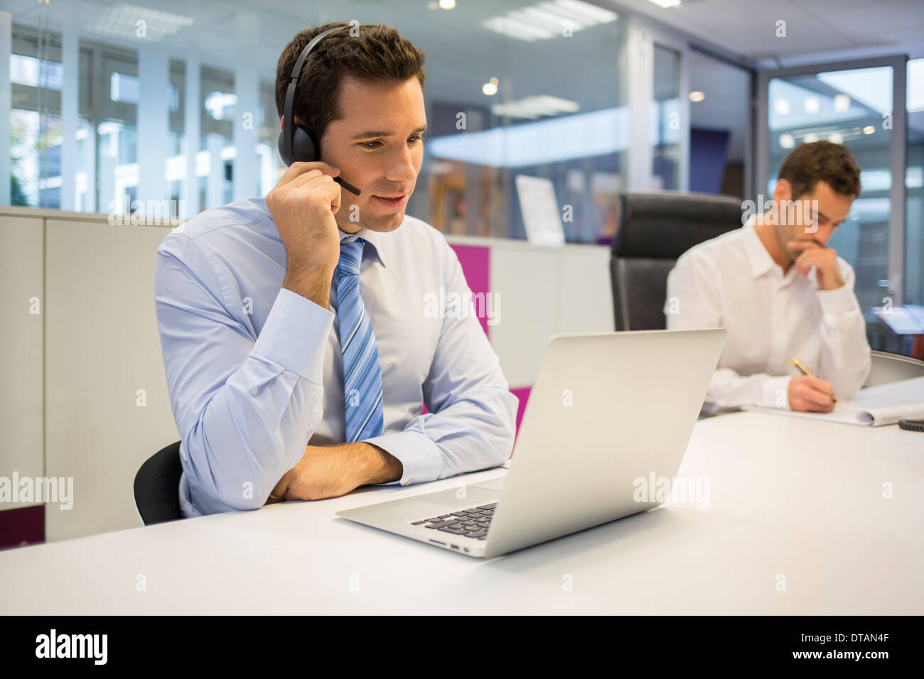 Businessman in office on phone with headset, call conference - Stock Image