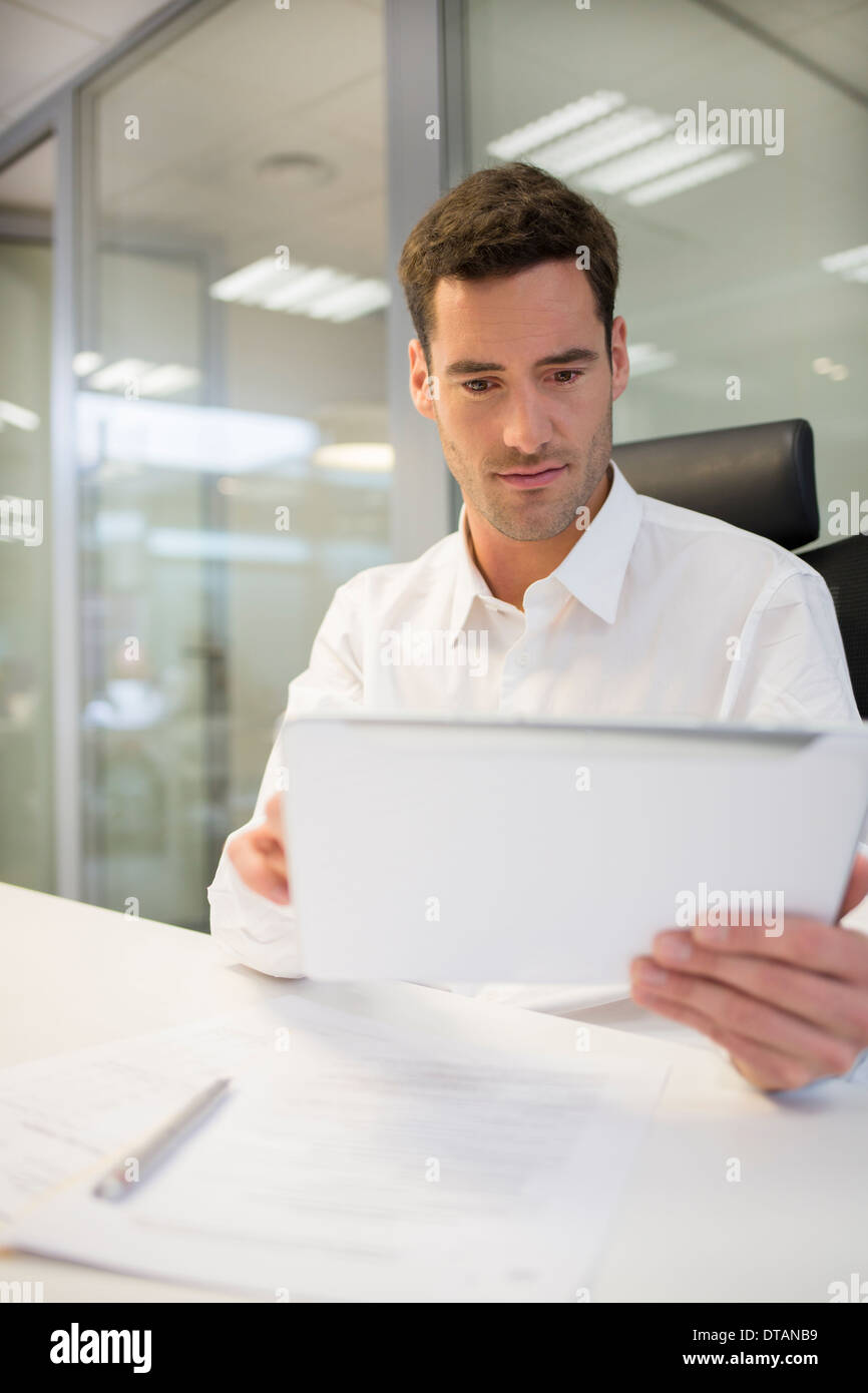 Businessman in office working on computer tablet Stock Photo