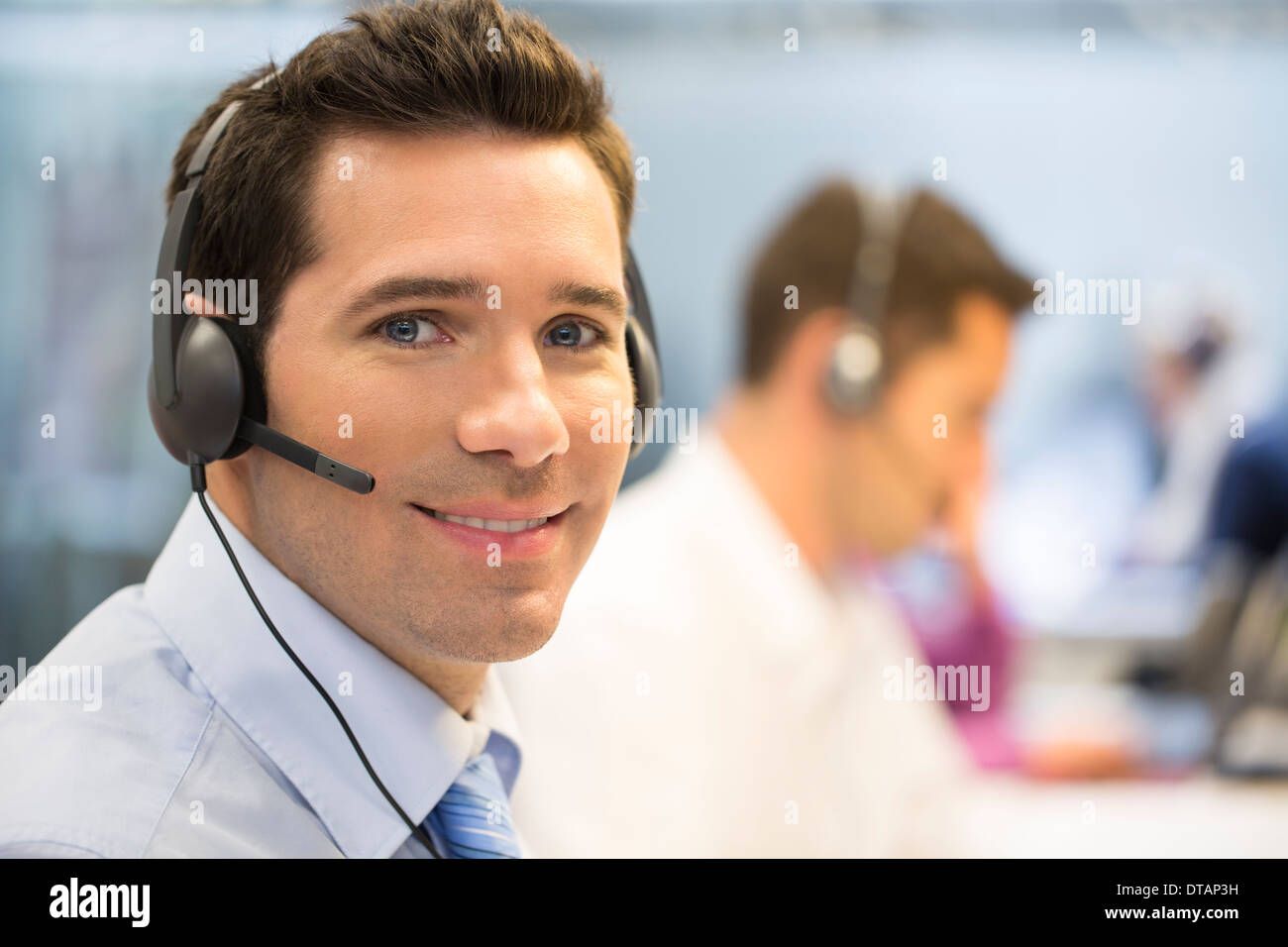Portrait of operator in office on phone with headset, looking camera - Stock Image