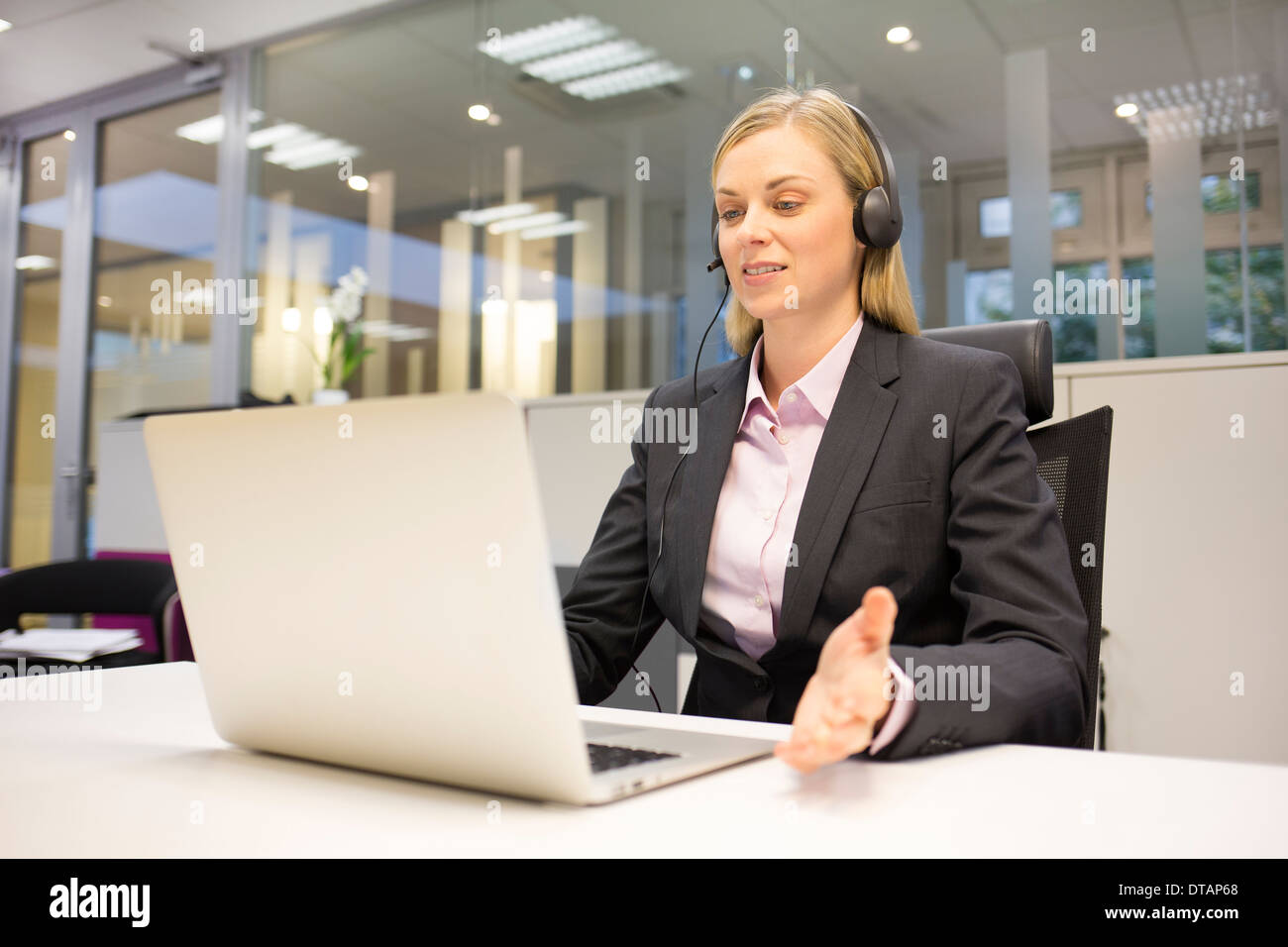 Pretty Businesswoman in office on phone with headset, video conference Stock Photo