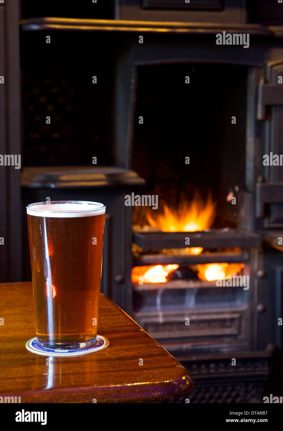 A pint of bitter on a pub table, with open fire in the background - Stock Image