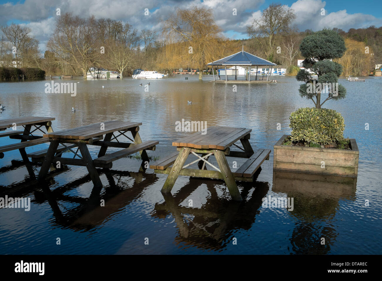 Flooded wooden trestle table and chairs and distant bandstand under River Thames floodwater Henley Oxfordshire UK - Stock Image