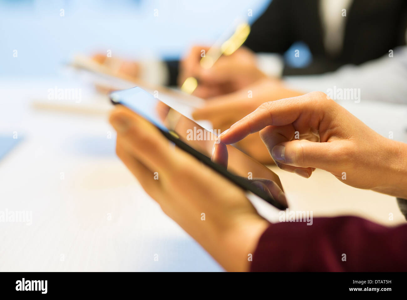Close-up of Businesswoman hands writing on digital tablet during a meeting - Stock Image