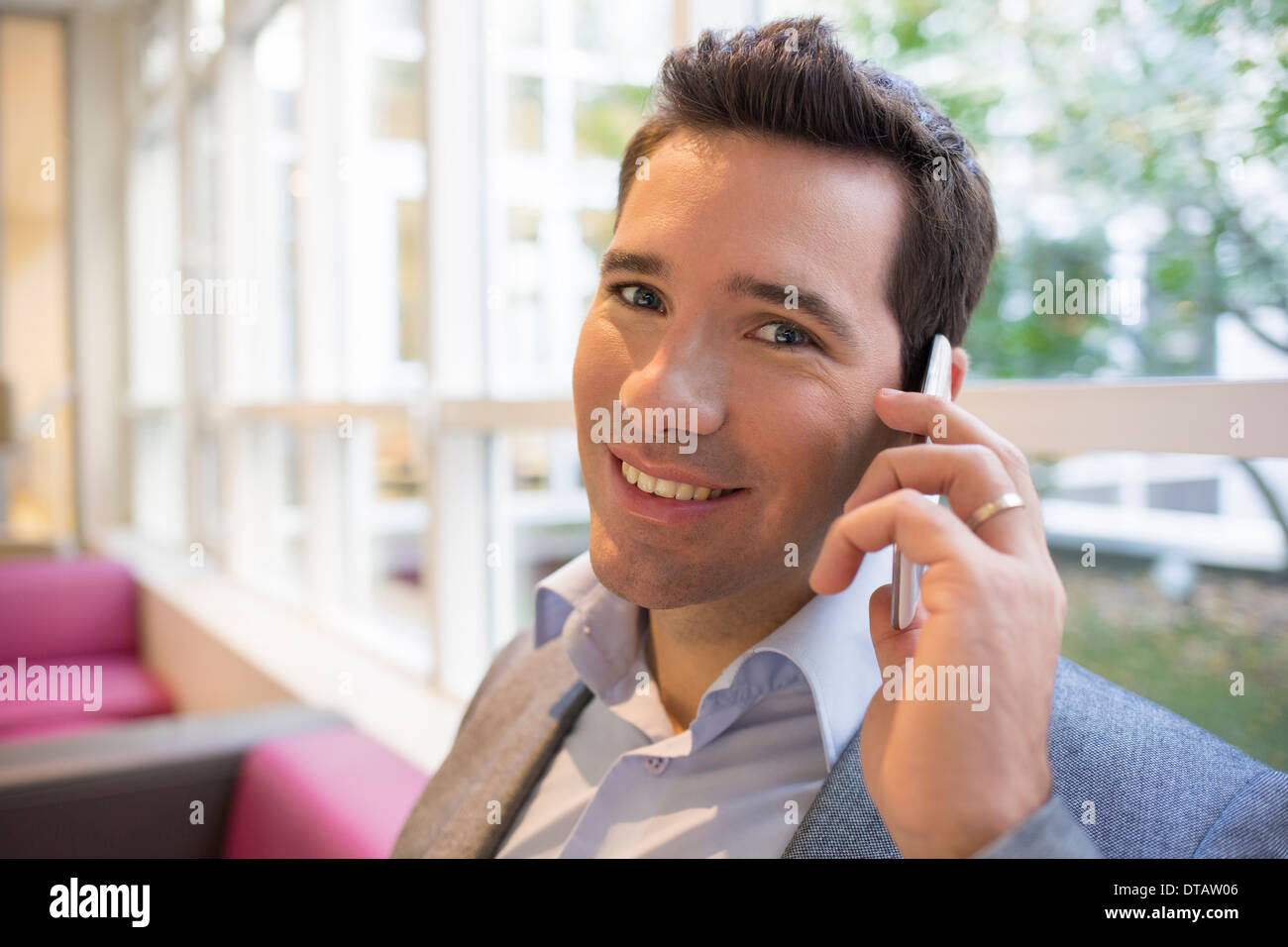 Happy smiling young Businessman on phone in office, looking camera Stock Photo