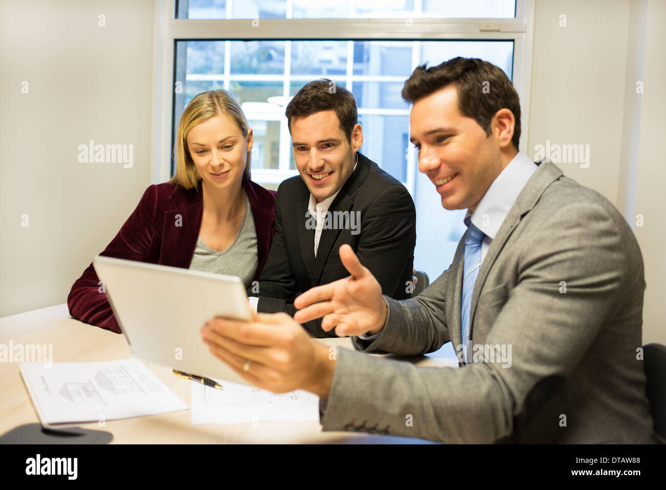 Couple meeting with real-estate agent to buy property, showing a project on tablet pc - Stock Image