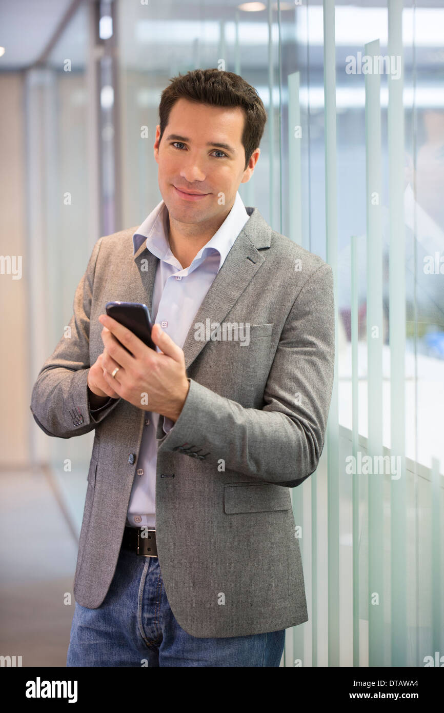Handsome businessman sending a message on cell phone in office, looking camera Stock Photo