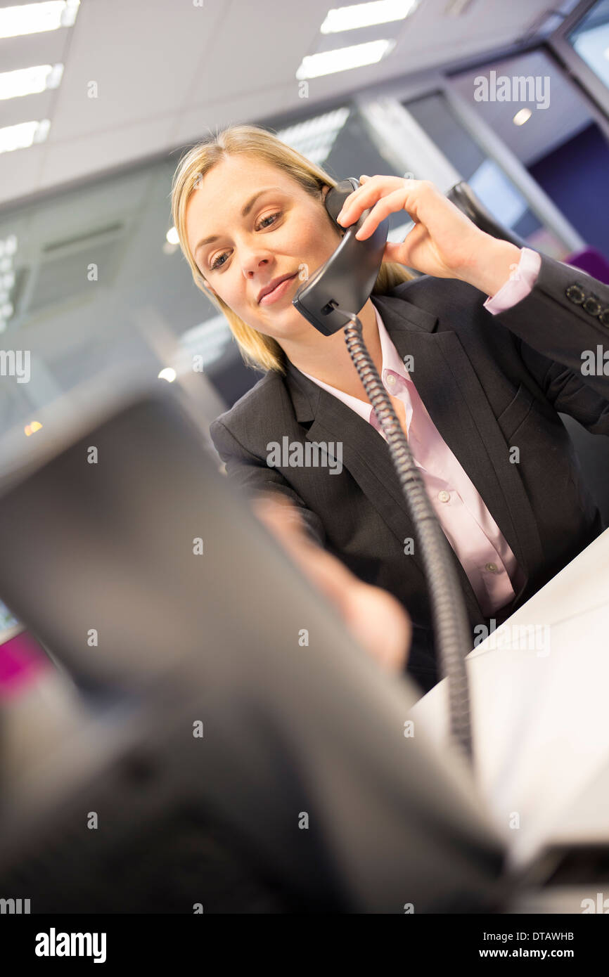 Businesswoman on phone in her office - Stock Image