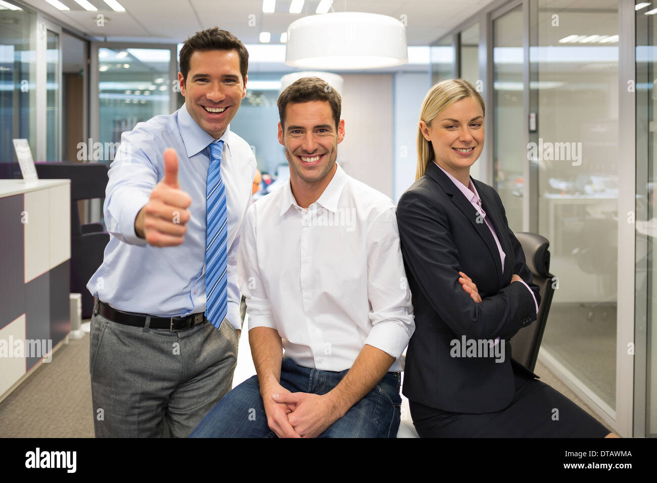 Portrait of joyful business team, man showing thumb up, office background - Stock Image