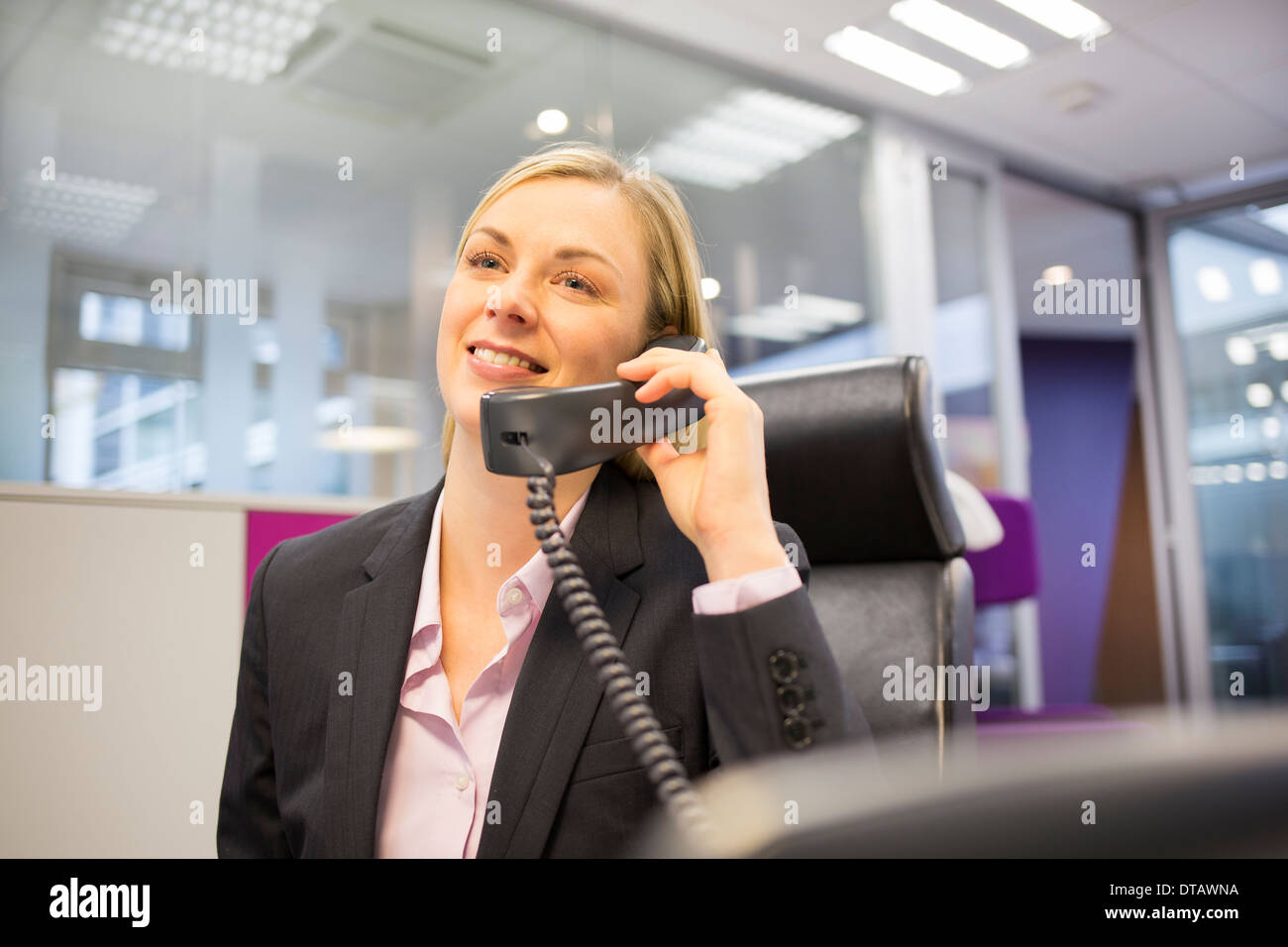 Blonde Businesswoman telephoning in her office Stock Photo