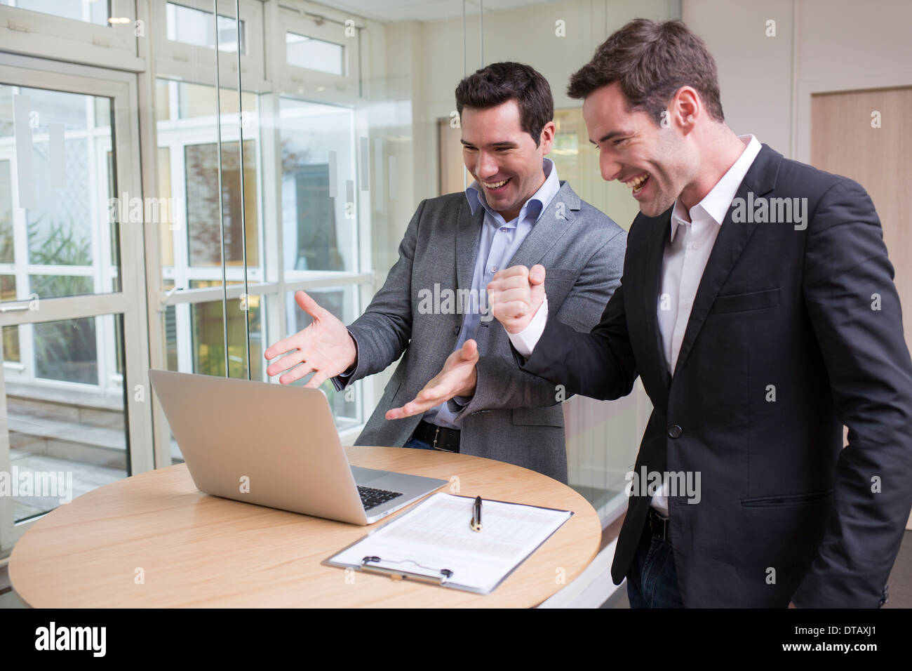 Successful smiling businessman in office, with arms up - Stock Image