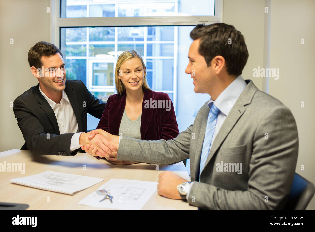 Couple in meeting room with financial adviser, contract, handshake, new property owners - Stock Image