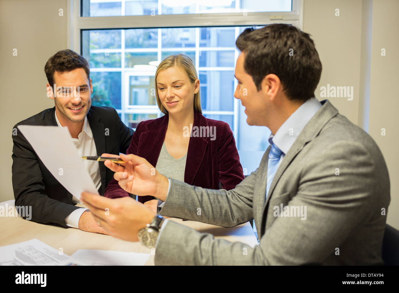 Young couple signing contract in office withe real-estate, new property owners - Stock Image