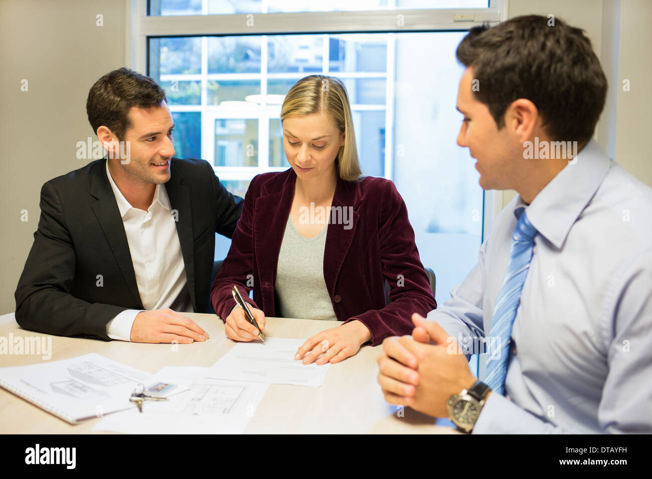 Young couple signing contract in office withe real-estate - Stock Image