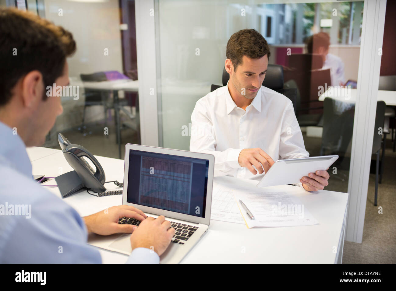 Two businessman working on computer in office, coworkers - Stock Image