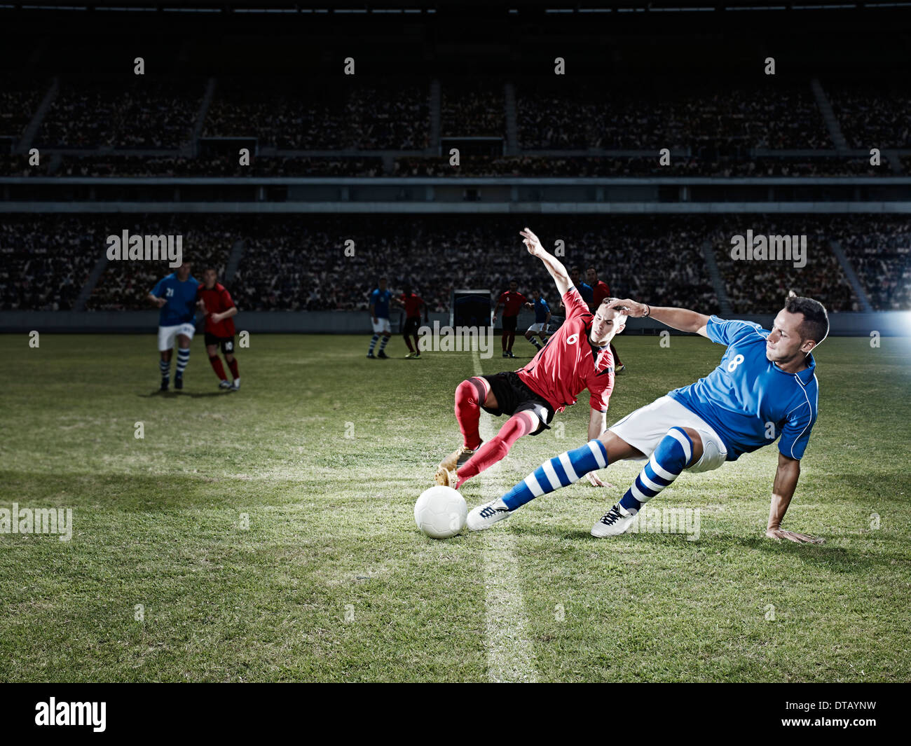 Soccer players kicking for ball on field - Stock Image