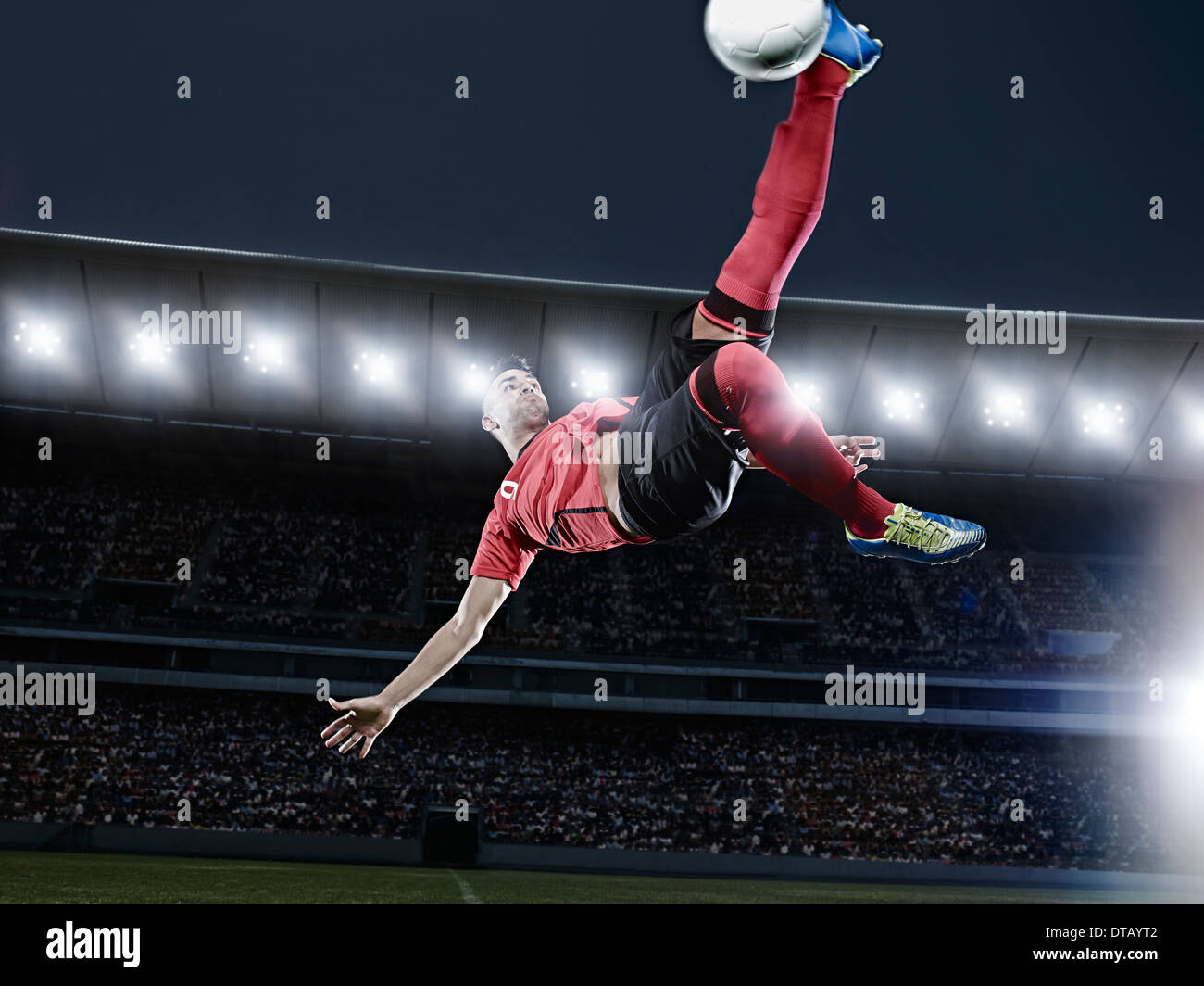Soccer player kicking ball in mid-air on field - Stock Image