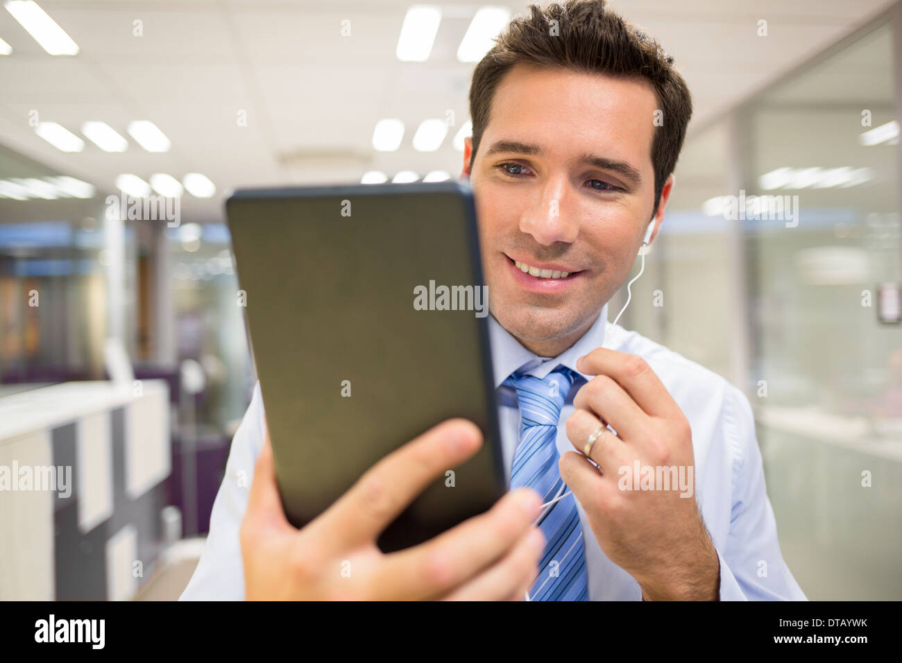 Portrait of businessman chatting in office withe digital tablet, skype - Stock Image