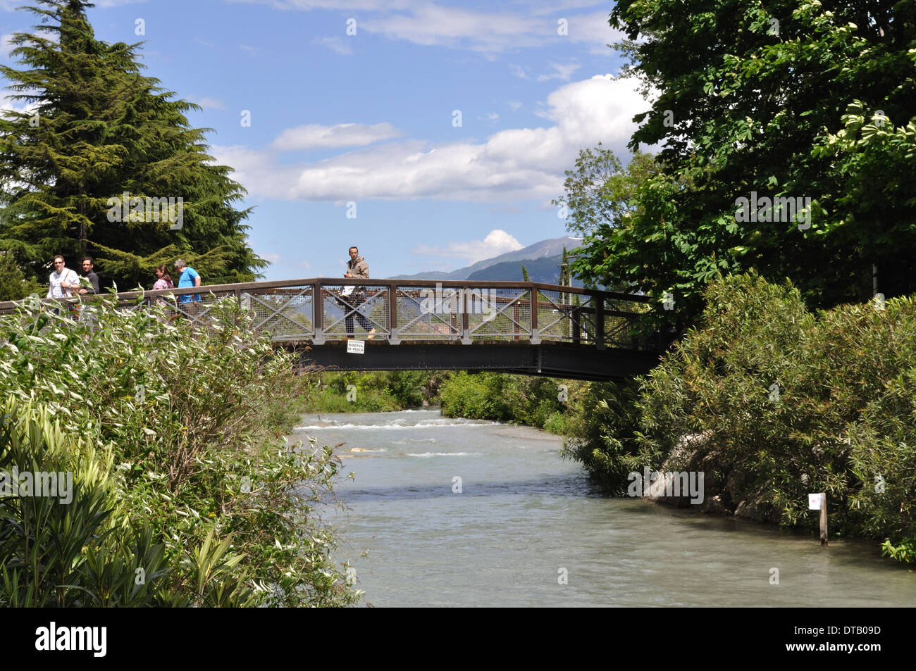 Footbridge over a river flowing into Lake Garda at Riva del Garda, Italy Stock Photo
