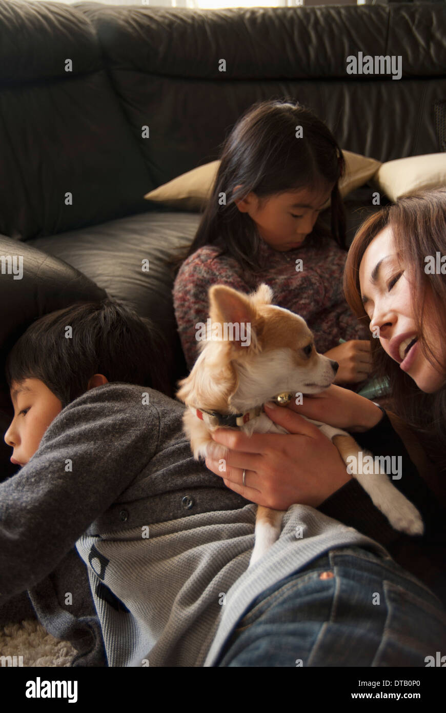 Family with dog in living room - Stock Image