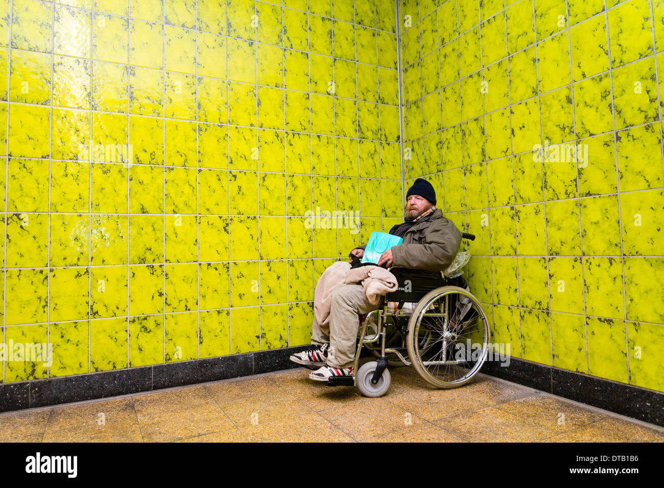 A homeless wheelchair user sits in 'his' corner, where he is living in an underground station. - Stock Image