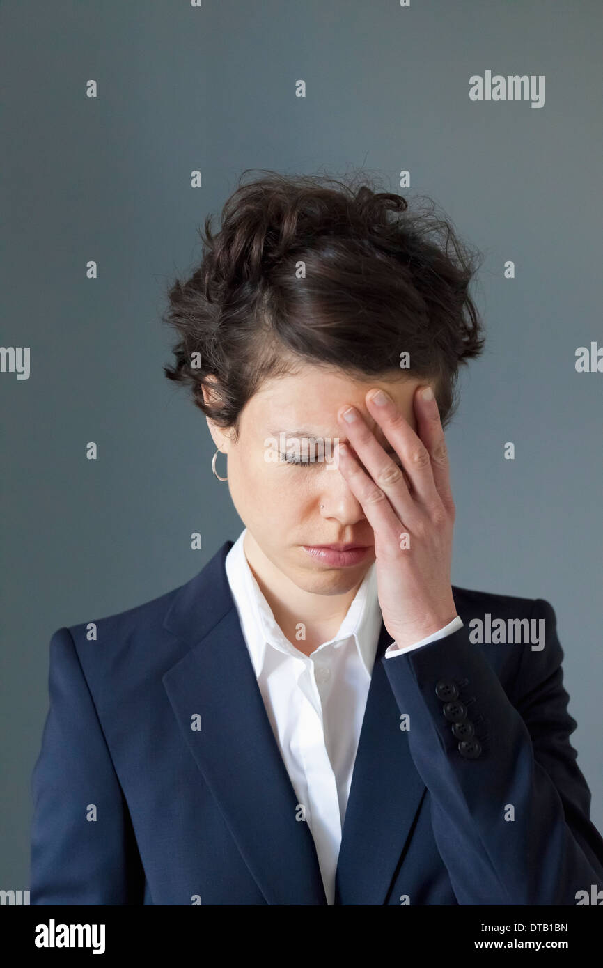 A stressed looking mid adult woman with hand covering face - Stock Image