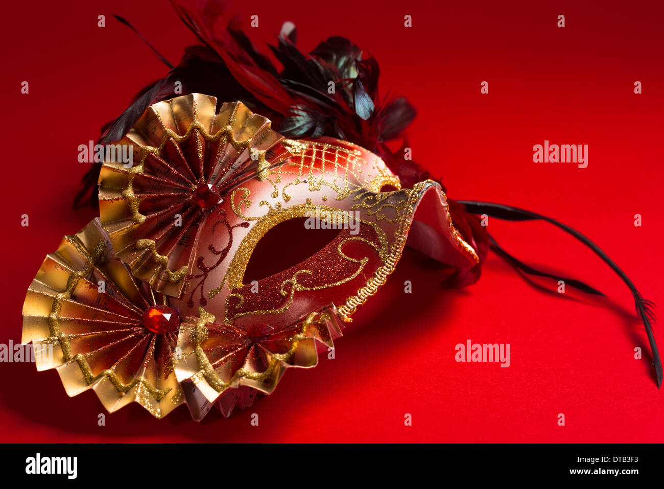 A red and gold venetian, mardi gras mask on a red background - Stock Image