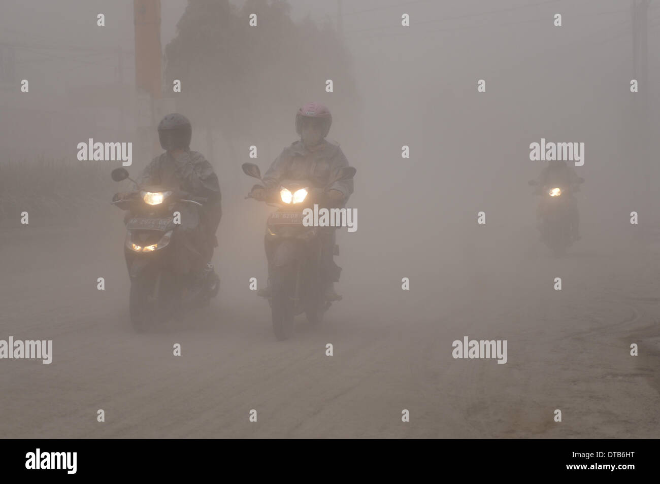 Yogyakarta, Indonesia. 14th Feb, 2014. Motorcyclists ride on an ash-covered road as rains of gravel and sand hit Yogyakarta province, Indonesia, Feb. 14, 2014. Mount Kelud in East Java, Indonesia, started eruption at 22:50 p.m. Jakarta time on Thursday, forcing thousands of residence living within 10 kilometers from the crater to evacuate, Umar Rosadi, a volcanologist at the national volcanology agency, told Xinhua by phone. Credit: Xinhua/Veri Sanovri/Alamy Live News - Stock Image