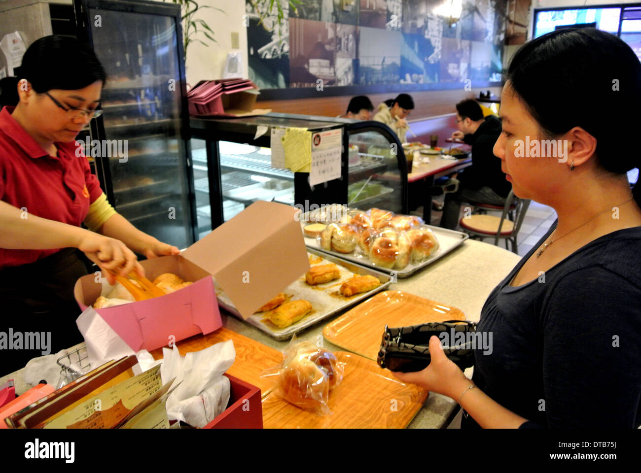 retail clerk packs pastries in box in chinatown restaurant - Stock Image