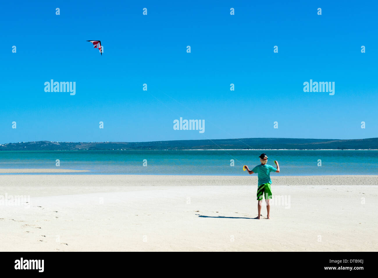 A boy flies his kite on the beach of a lagoon, Churchhaven, Western Cape, South Africa - Stock Image