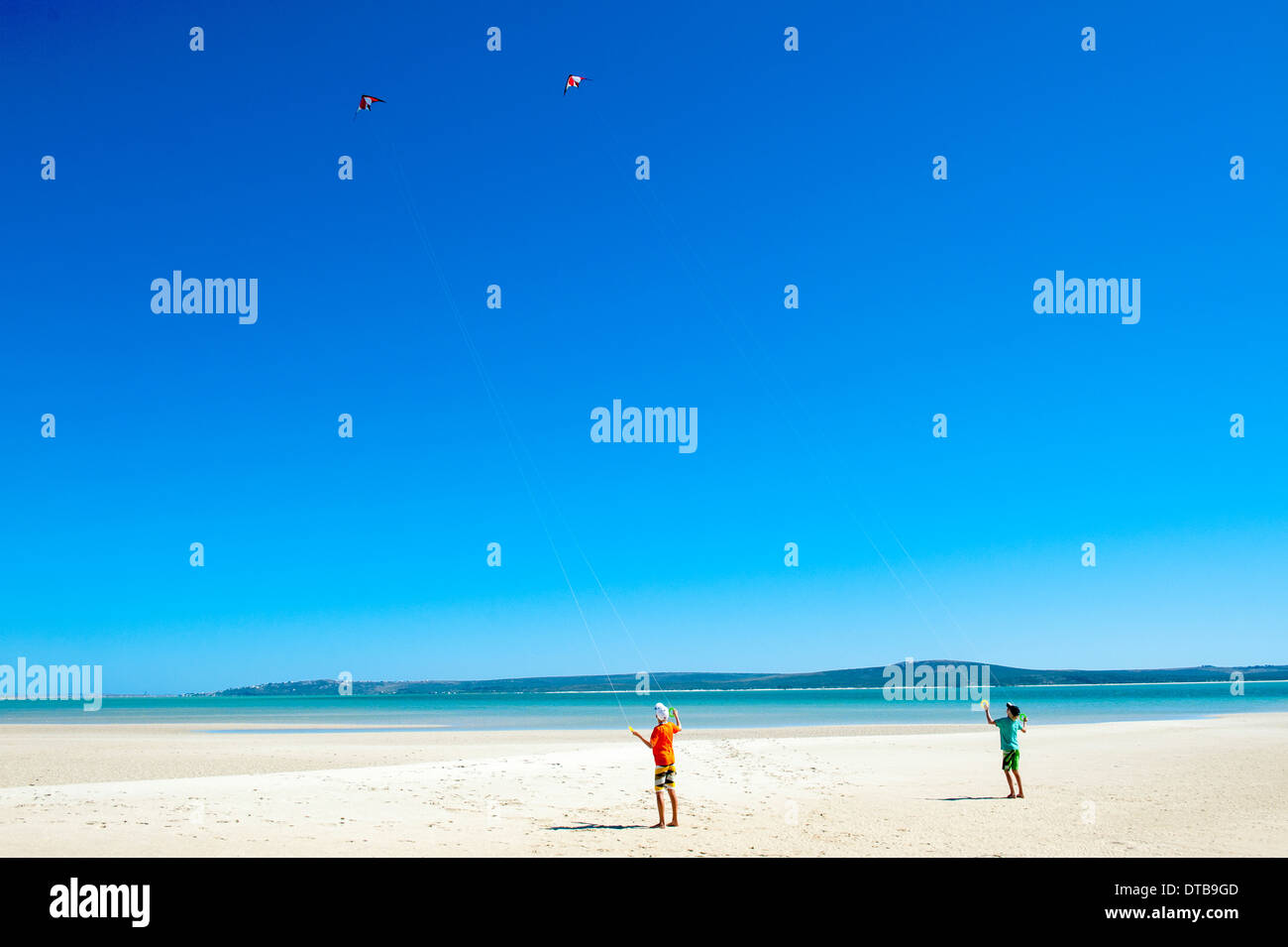 Two boys flying kites on the beach of a lagoon, Churchhaven, Western Cape, South Africa - Stock Image