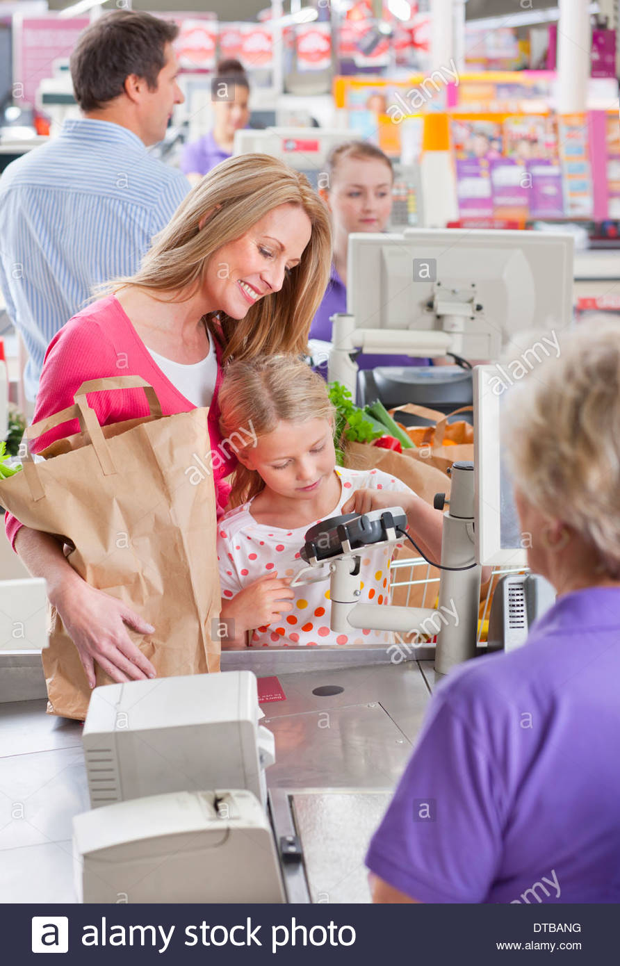 Mother And Daughter Paying For Shopping At Supermarket Checkout - Stock Image