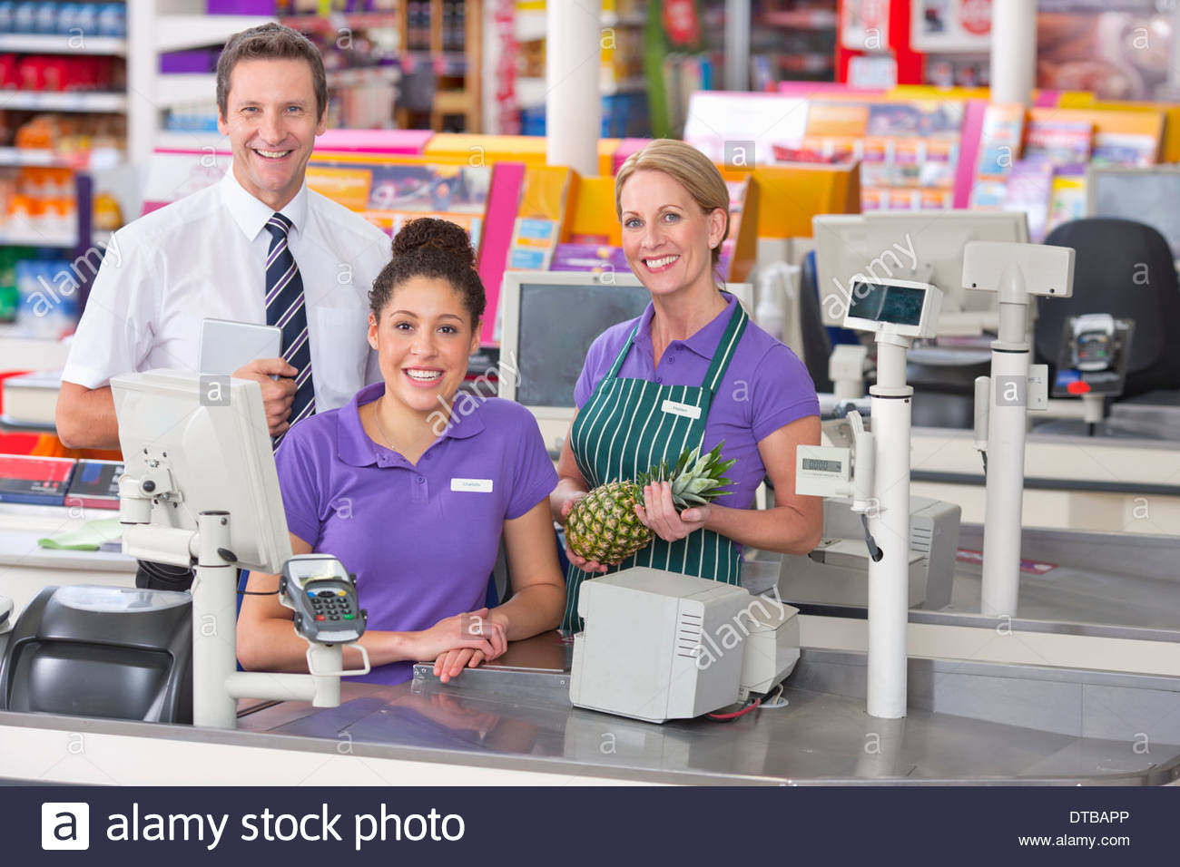 Portrait Of Supermarket Staff At Checkout - Stock Image