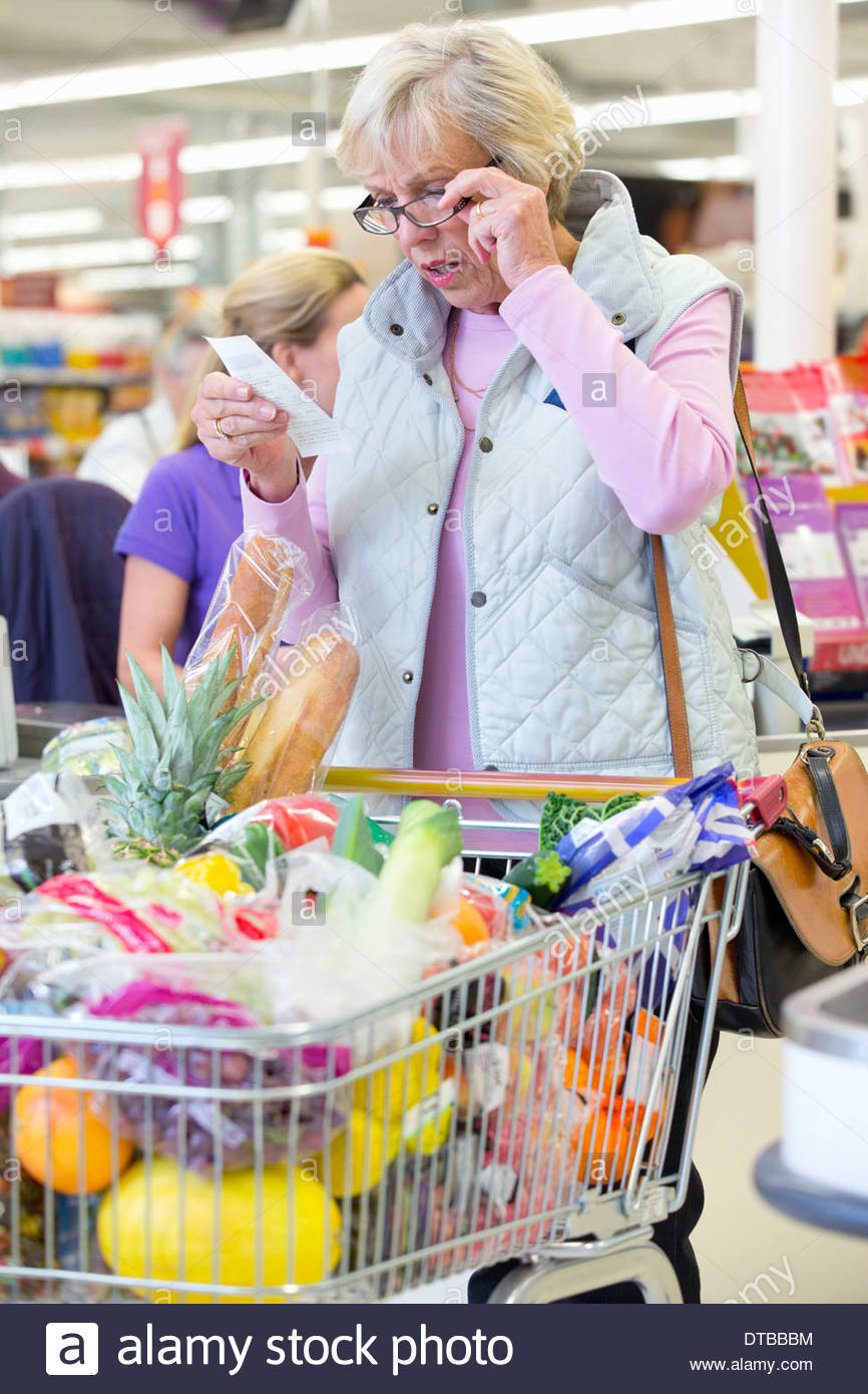 Shocked Customer With Shopping At Supermarket Checkout - Stock Image