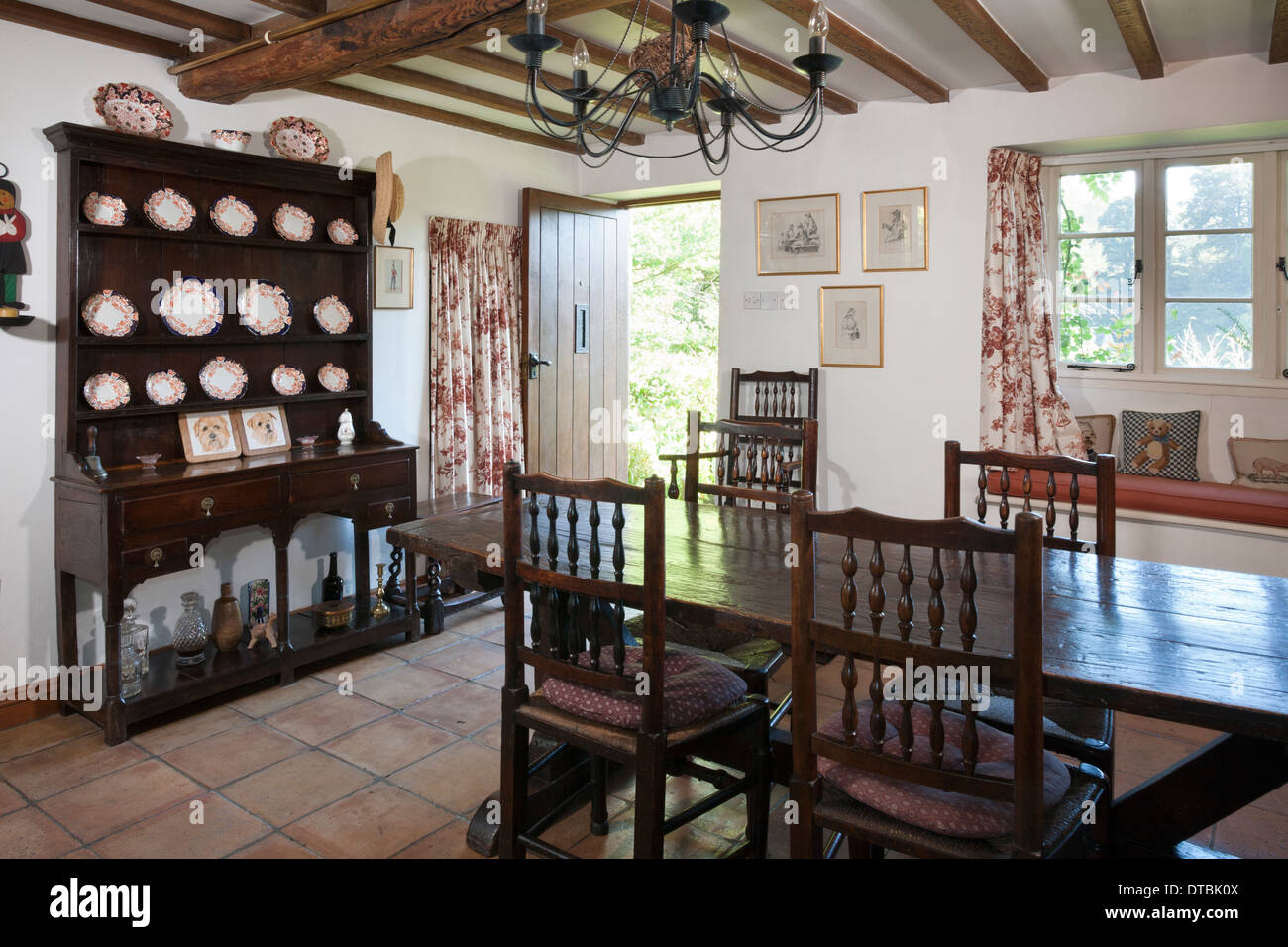 Period Small Cottage Dining Room With Tile Floor Oak Furniture And Front Door Open