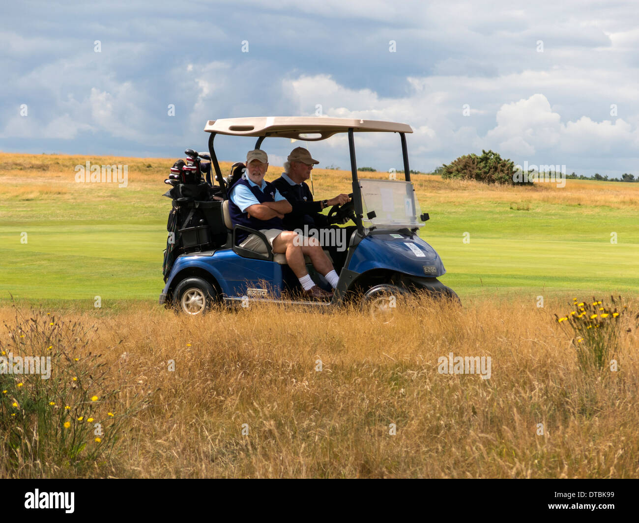 Men riding in golf buggy across golf course in Cromer Norfolk England - Stock Image