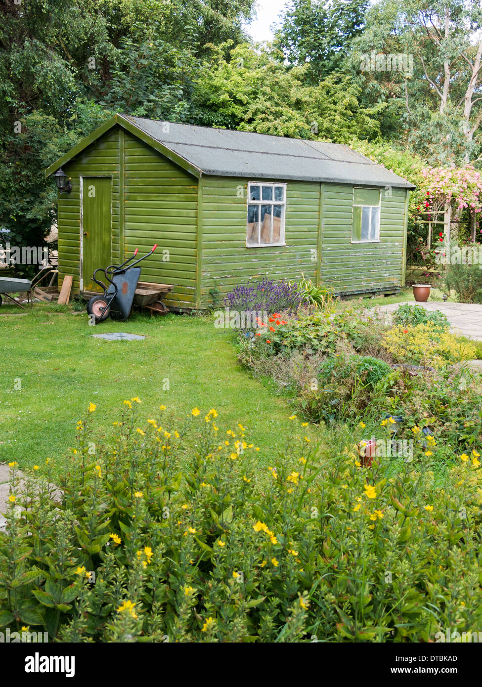 Large Green Garden Shed With Lawn And Wheelbarrow In Front