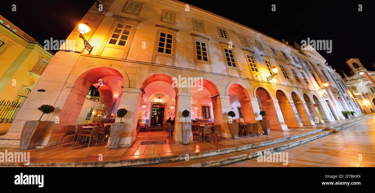 Portugal, Algarve: Nocturnal illuminated arcade building of the 'Columbus Bar' in Faro - Stock Image