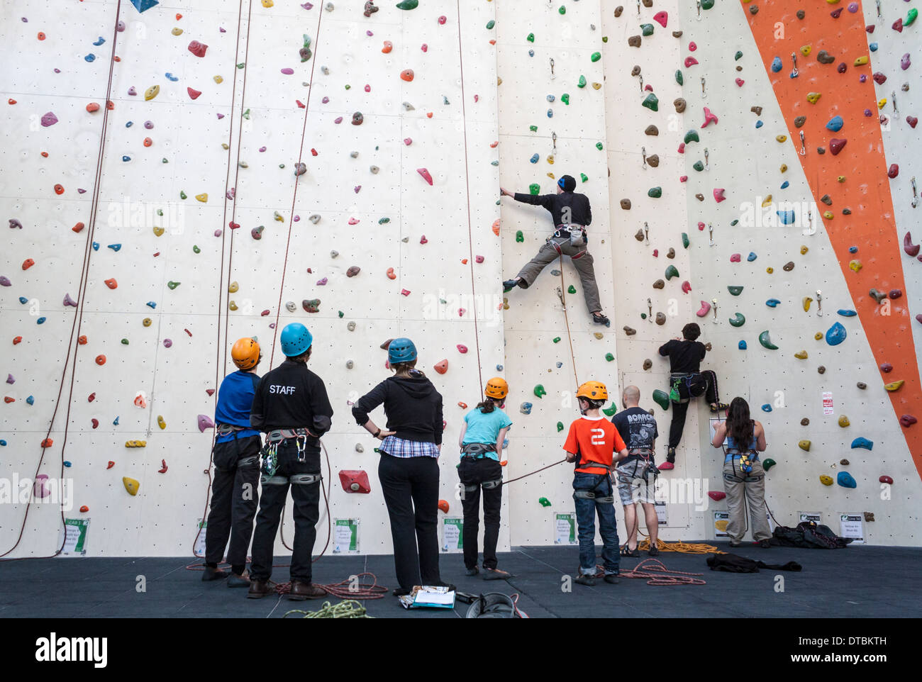 Children and adults take a climbing lesson on an indoor climbing wall. - Stock Image