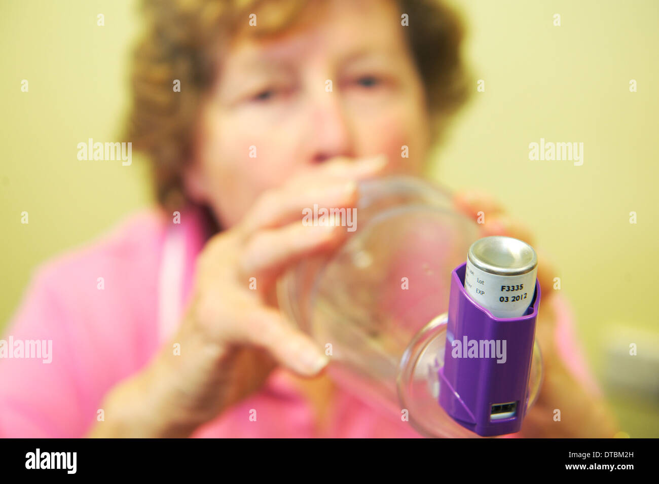 Patient using an inhaler and spacer during COPD clinic. Close up view, with patient looking at camera - Stock Image
