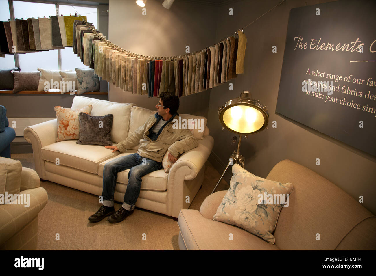 Man Trying out Couches in Store - London UK - Stock Image