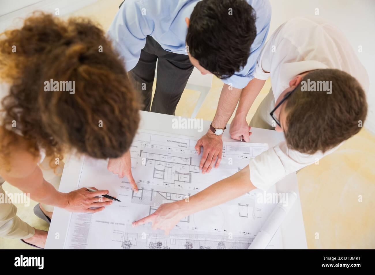 Business people analyzing blueprint - Stock Image
