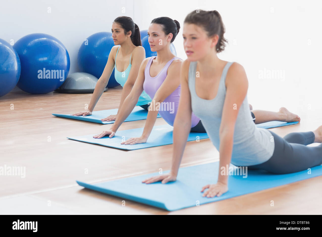 Class doing the cobra pose in fitness studio Stock Photo