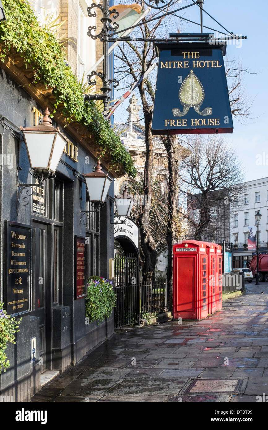 The Mitre Hotel free house pub sign and traditional red telephone boxes in Greenwich London, UK - Stock Image