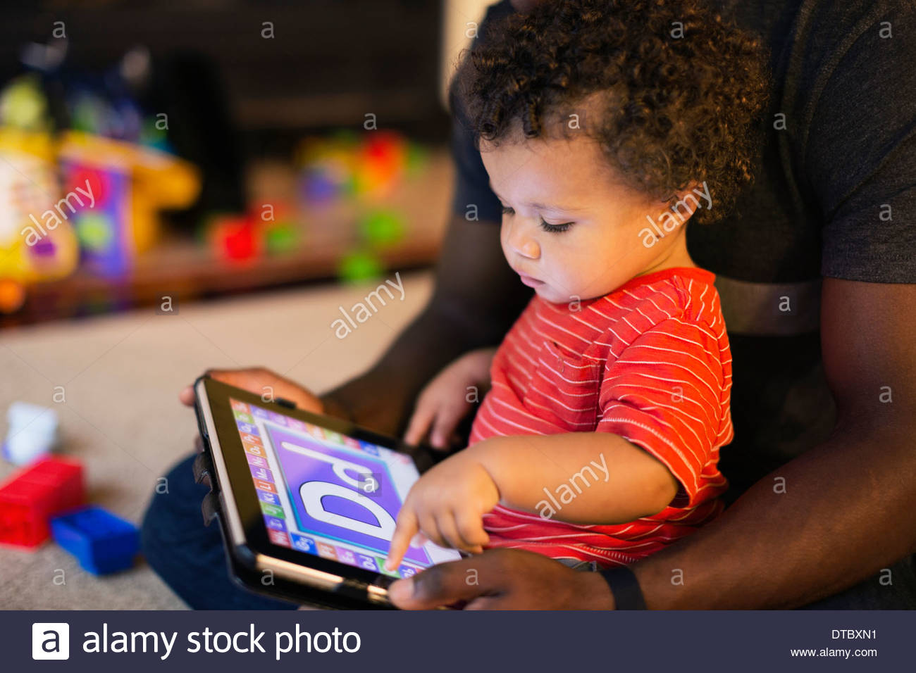 Father and son playing with digital tablet - Stock Image