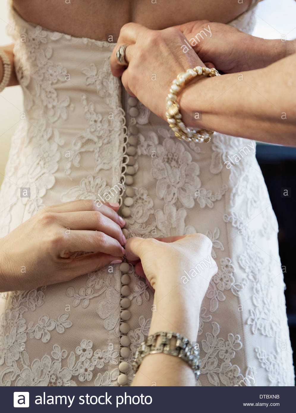 Bride being helped to get into wedding dress - Stock Image