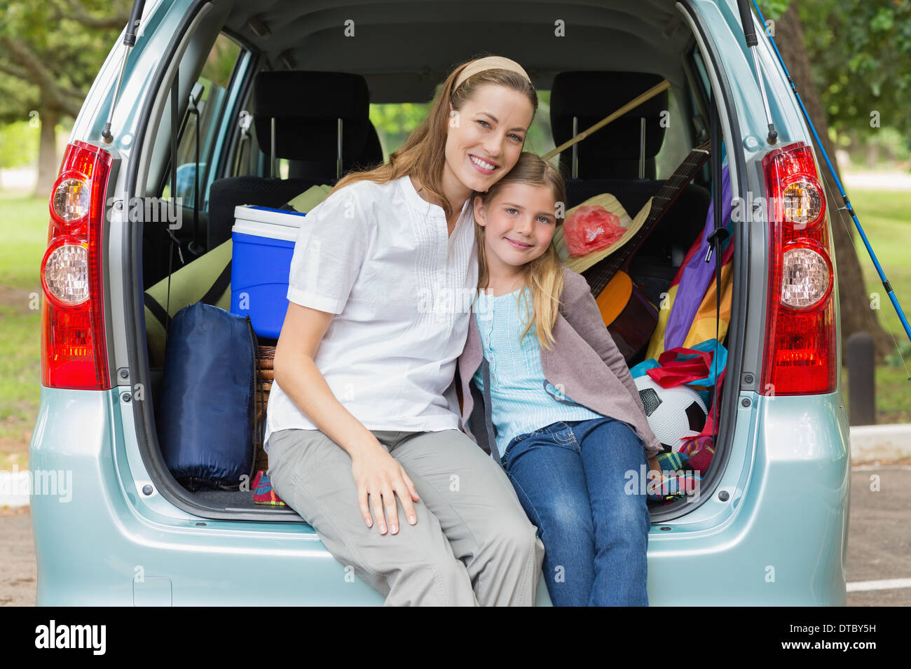 Smiling mother and daughter sitting in car trunk - Stock Image